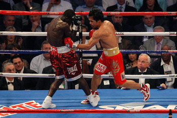 ARLINGTON, TX - MARCH 13:  (R-L) Manny Pacquiao of the Philippines throws a left to the body of Joshua Clottey of Ghana during the WBO welterweight title fight at Cowboys Stadium on March 13, 2010 in Arlington, Texas. Pacquiao defeated Clottey by unanimou