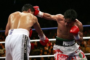 LAS VEGAS - JANUARY 21:  (R-L) Manny Pacquiao of the Phillippines lands a right on Erik Morales of Mexico during their Super Featherweight Championship fight at Thomas & Mack Arena on January 21, 2006 in Las Vegas, Nevada. Pacquiao defeated Morales by a 1