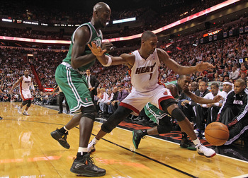 MIAMI - NOVEMBER 11:  Chris Bosh #1 of the Miami Heat chases a loose ball against Kevin Garnett #5 and Rajon Rondo #9  during a game against the Boston Celtics at American Airlines Arena on November 11, 2010 in Miami, Florida. NOTE TO USER: User expressly