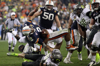 GLENDALE, AZ - JANUARY 10:  Cameron Newton #2 of the Auburn Tigers is brought down by John Boyett #20 of the Oregon Ducks during the Tostitos BCS National Championship Game at University of Phoenix Stadium on January 10, 2011 in Glendale, Arizona.  (Photo
