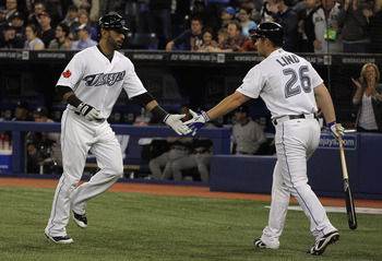 TORONTO, ON - APRIL 19:  Jose Bautista #19 (L) of the Toronto Blue Jays celebrates with teammate Adam Lind #26 after Bautista's first inning home run during their game against the New York Yankees at Rogers Centre on April 19, 2011 in Toronto, Canada.  (P