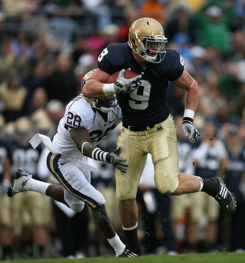 SOUTH BEND, IN - OCTOBER 03: Kyle Rudolph #9 of the Notre Dame Fighting Irish breaks away from Quinton Rochardson #28 of the Washington Huskies after catching the ball on October 3, 2009 at Notre Dame Stadium in South Bend, Indiana. (Photo by Jonathan Dan