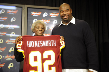 ASHBURN, VA - FEBRUARY 27:  Albert Haynesworth #92 and his mom Linda pose with his team jersey at a press conference after signing a 7-year contract worth approximately $100 million with the Washington Redskins on February 27, 2009 at Redskins Park in Ash