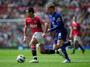 MANCHESTER, ENGLAND - APRIL 23:  Javier Hernandez of Manchester United skips past Phil Neville of Everton during the Barclays Premier League match between Manchester United and Everton at Old Trafford on April 23, 2011 in Manchester, England.  (Photo by S