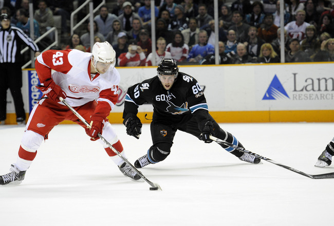 SAN JOSE, CA - MARCH 3: Jason Demers #60 of the San Jose Sharks defends Darren Helm #43 of the Detroit Red Wings in the third period of an NHL hockey game at the HP Pavilion on March 3, 2011 in San Jose, California. The Sharks won the game 3-1. (Photo by