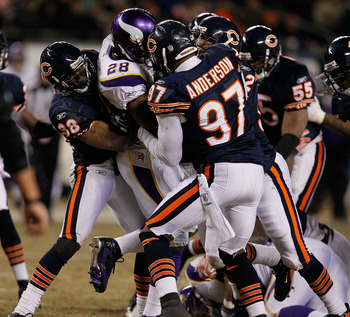 CHICAGO - DECEMBER 28: Adrian Peterson #28 of the Minnesota Vikings is gang-tackled by members of the Chicago Bears including Danieal Manning #38 and Mark Anderson #97 at Soldier Field on December 28, 2009 in Chicago, Illinois. The Bears defeated the Viki