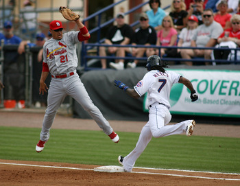 PORT ST. LUCIE, FL - MARCH 03: First baseman Allen Craig #21 of the St. Louis Cardinals cannot make a play on Jose Reyes #7 of the New York Mets at Digital Domain Park on March 3, 2011 in Port St. Lucie, Florida.  (Photo by Marc Serota/Getty Images)