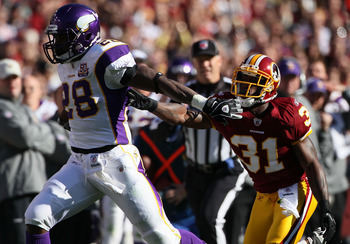 LANDOVER, MD - NOVEMBER 28: Running back Adrian Peterson #28 of the Minnesota Vikings stiff arms Philip Buchanon #31 the Washington Redskins at FedExField November 28, 2010 in Landover, Maryland. The Vikings won the game 17-13. (Photo by Win McNamee/Getty
