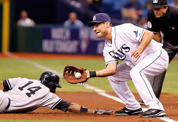 ST. PETERSBURG, FL - JULY 18:  Infielder Casey Kotchman #11 of the Tampa Bay Rays takes the throw at first as Curtis Granderson #14 of the New York Yankees gets back safely during the game at Tropicana Field on July 18, 2011 in St. Petersburg, Florida.  (