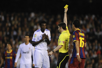 VALENCIA, SPAIN - APRIL 20:  Referee Alberto Undiano Mallenco shows the yellow card to Adebayor of Real Madrid (L) during the Copa del Rey Final between Real Madrid and Barcelona at Estadio Mestalla on April 20, 2011 in Valencia, Spain.  (Photo by David R