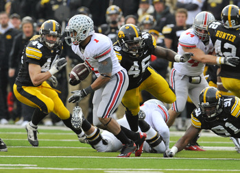 IOWA CITY, IA - NOVEMBER 20:  Tailback Dan Herron #1 of the Ohio State Buckeyes scrambles for yards past defensive end Christian Ballard $46 of the University of Iowa Hawkeyes during the second half of play at Kinnick Stadium on November 20, 2010 in Iowa
