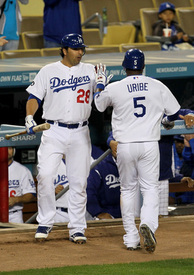 LOS ANGELES - APRIL 29:   Juan Uribe #5 of the Los Angeles Dodgers is greeted by Rod Barajas #28 as he returns to the dugout after hitting a solo home run in the fourth inning against the San Diego Padres on April 29, 2011 at Dodger Stadium in Los Angeles