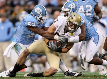 CHARLOTTE, NC - DECEMBER 26:  Mike Shanahan #87 of the Pittsburgh Panthers is tackled by teammates Quan Sturdivant #52 and Bruce Carter #54 of the North Carolina Tar Heels during their game on December 26, 2009 in Charlotte, North Carolina.  (Photo by Str