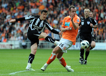 BLACKPOOL, ENGLAND - APRIL 23: Joey Barton of Newcastle United shoots at goal as Charlie Adam of Blackpool blocks during the Barclays Premier League match between Blackpool and Newcastle United at Bloomfield Road on April 23, 2011 in Blackpool, England.