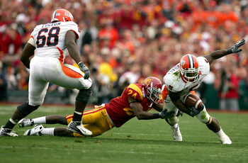 PASADENA, CA - JANUARY 01:  Running back Rashard Mendenhall #5 of the Illinois Fighting Illini is tackled by Shareece Wright #24 of the USC Trojans during the first half of the 'Rose Bowl presented by Citi' at the Rose Bowl on January 1, 2008 in Pasadena,