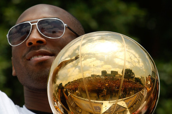 LOS ANGELES, CA - JUNE 21:  The crowd is reflected in the championship trophy held by Los Angeles Lakers guard Kobe Bryant as he rides in the victory parade for the the NBA basketball champion team on June 21, 2010 in Los Angeles, California. The Lakers b