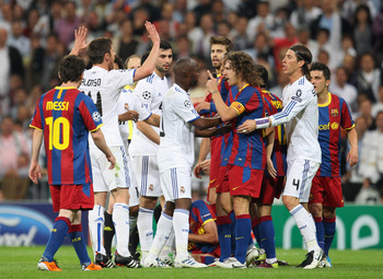 MADRID, SPAIN - APRIL 27:  Lassana Diarra of Real Madrid and Carles Puyol of Barcelona clash during the UEFA Champions League Semi Final first leg match between Real Madrid and Barcelona at Estadio Santiago Bernabeu on April 27, 2011 in Madrid, Spain.  (P