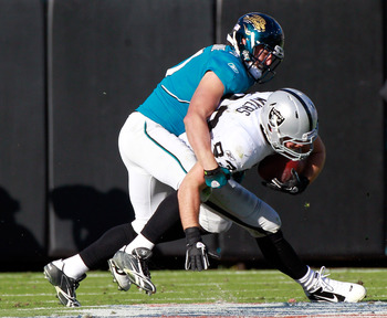 JACKSONVILLE, FL - DECEMBER 12:  Sean Considine #37 of the Jacksonville Jaguars tackles Brandon Myers #83 of the Oakland Raiders during the game at EverBank Field on December 12, 2010 in Jacksonville, Florida.  (Photo by Sam Greenwood/Getty Images)