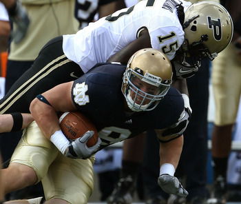 SOUTH BEND, IN - SEPTEMBER 04: Kyle Rudolph #9 of the Notre Dame Fighting Irish is tackled by Charlton Williams #15 of the Purdue Boilermakers at Notre Dame Stadium on September 4, 2010 in South Bend, Indiana. Notre Dame defeated Purdue 23-12. (Photo by J