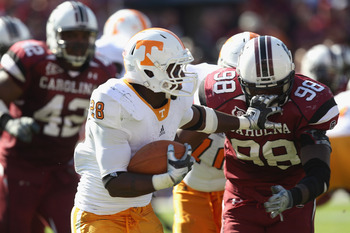 COLUMBIA, SC - OCTOBER 30:  Tauren Poole #28 of the Tennessee Volunteers grabs the facemask of Devin Taylor #98 of the South Carolina Gamecocks during their game at Williams-Brice Stadium on October 30, 2010 in Columbia, South Carolina.  (Photo by Streete