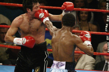 LAS VEGAS - SEPTEMBER 13:  Oscar De La Hoya takes a punch in the face from Shane Mosley on September 13, 2003 at the MGM Grand in Las Vegas, Nevada.  Mosley defeated De La Hoya by unanimous decision.  (Photo by Jeff Gross/Getty Images)