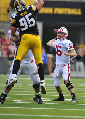 IOWA CITY, IA - OCTOBER 23: Quarterback Scott Tolzien #16 of the Wisconsin Badgers throws under pressure from Defensive lineman Karl Klug #95 of the University of Iowa Hawkeyes during the first half of play at Kinnick Stadium on October 23, 2010 in Iowa C