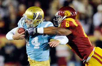 LOS ANGELES, CA - NOVEMBER 28:  Quarterback Kevin Prince #14 of the UCLA Bruins is tackled by Malcolm Smith #6 of the USC Trojans during the second quarter of the NCAA college football game at Los Angeles Memorial Coliseum on November 28, 2009 in Los Ange
