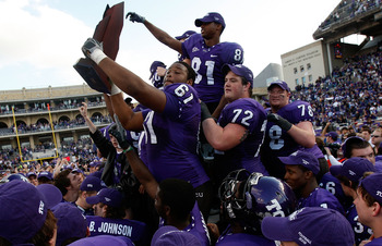 FORT WORTH, TX - NOVEMBER 28:  Marcus Cannon #61, Kyle Dooley #72 and Alonzo Adams #81 of the TCU Horned Frogs raise the Mountain West Regular Season Championship trophy at Amon G. Carter Stadium on November 28, 2009 in Fort Worth, Texas.  (Photo by Ronal