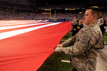 INDIANAPOLIS, IN - JANUARY 08:  Military personnel stretch out a giant AMerican Flag for the performance of the Nation Anthem prior to the Indianapolis Colts hosting the New York Jets during their 2011 AFC wild card playoff game at Lucas Oil Stadium on Ja