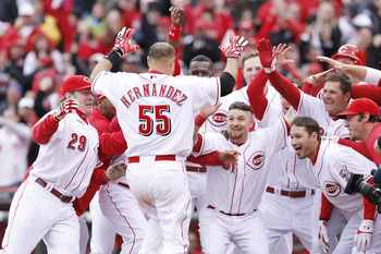 CINCINNATI, OH - MARCH 31: Ramon Hernandez #55 of the Cincinnati Reds celebrates at home plate with teammates after hitting the game-winning home run in the ninth inning against the Milwaukee Brewers in the opening day game at Great American Ballpark on M