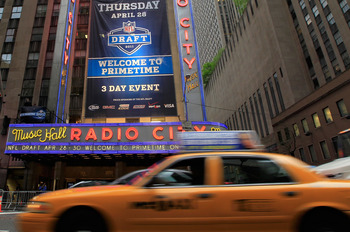 NEW YORK, NY - APRIL 28:  Taxi cabs drive down the Avenue of the Americas past the Radio City Music Hall marquee, site of the 2011 NFL Draft, on April 28, 2011 in New York City.  (Photo by Chris Trotman/Getty Images)