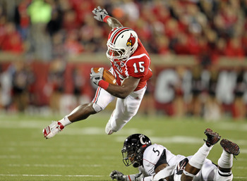 LOUISVILLE, KY - OCTOBER 15:  Bilal Powell #15 of  the Louisville Cardinals runs with the ball while tackled by Reuben Johnson #5 of the Cincinnati Bearcats during the game at Papa John's Cardinal Stadium on October 15, 2010 in Louisville, Kentucky.  (Pho