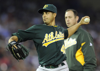 MINNEAPOLIS, MN - APRIL 9: Starting pitcher Gio Gonzalez #47 of the Oakland Athletics throws while athletic trainer Nick Paparesta looks on during the fifth inning of their game on April 9, 2011 at Target Field in Minneapolis, Minnesota. Athletics defeate