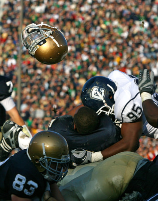 SOUTH BEND, IN - NOVEMBER 21: Armando Allen #5 of the Notre Dame Fighting Irish looses his helmut as he is hit at the goalline by Greg Lloyd #95 of the Univeristy of Connecticut Huskies at Notre Dame Stadium on November 21, 2009 in South Bend, Indiana. (P