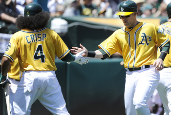 OAKLAND, CA - MAY 1:  Daric Barton  (R) slaps hand with teammate Coco Crisp #4 of the Oakland Athletics after they both scored on Conor Jackson's double in the bottom of the first inning against the Texas Rangers during a MLB baseball game at the Oakland-