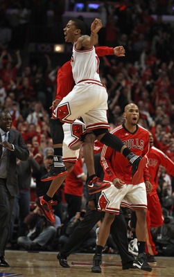 CHICAGO, IL - APRIL 16: Derrick Rose #1 of the Chicago Bulls jumps in the air with teammate C.J. Watson #32 as Taj Gibson #22 runs onto the court in celebratiuon of a win against the Indiana Pacers in Game One of the Eastern Conference Quarterfinals in th