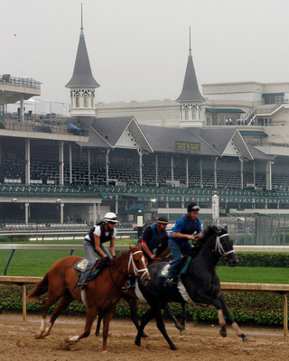 With the famous twin spires as a backdrop, a horses and riders work out before racing  at Churchill Downs May 4, 2007 in Louisville. (Photo by A. Messerschmidt/Getty Images) *** Local Caption ***