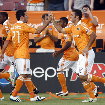 HOUSTON - APRIL 29:  Forward Will Bruin #12 of the Houston Dynamo is congratulated by Hunter Freeman #21after scoring in the first half against D.C. United at Robertson Stadium on April 29, 2011 in Houston, Texas.  (Photo by Bob Levey/Getty Images)