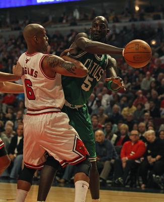 CHICAGO, IL - APRIL 07: Kevin Garnett #5 of the Boston Celtics passes the ball around Keith Bogans #6 of the Chicago Bulls at United Center on April 7, 2011 in Chicago, Illinois. NOTE TO USER: User expressly acknowledges and agrees that, by downloading an