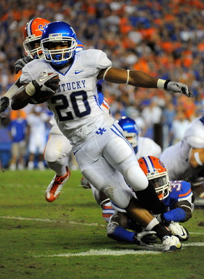 GAINESVILLE, FL - SEPTEMBER 25:  Running back Derrick Locke #20 of the Kentucky Wildcats is brought down by safety Ahmad Black #35 of the Florida Gators at Ben Hill Griffin Stadium on September 25, 2010 in Gainesville, Florida.  (Photo by Doug Benc/Getty
