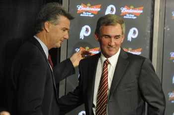 ASHBURN,VA - JANUARY 6:  Mike Shanahan, the new Executive Vice President and head coach of the Washington Redskins and Bruce Allen Executive Vice President shake hands before a press conference welcoming Shanahan to the Redskins on January 6, 2010 at Reds