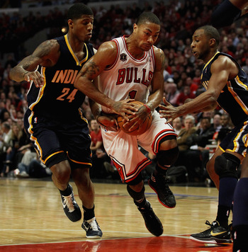 CHICAGO, IL - APRIL 18: Derrick Rose #1 of the Chicago Bulls drives between Paul George #24 and A.J. Price #12 of the Indiana Pacers in Game Two of the Eastern Conference Quarterfinals in the 2011 NBA Playoffs at the United Center on April 18, 2011 in Chi