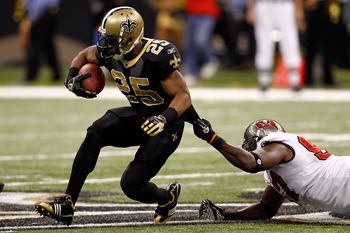 NEW ORLEANS, LA - JANUARY 02:  Reggie Bush #25  of the New Orleans Saints is tackled by Alex Magee #97 of the Tampa Bay Buccaneers at the Louisiana Superdome on January 2, 2011 in New Orleans, Louisiana.   The Buccaneers defeated the Saints 23-13.  (Photo
