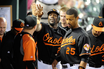 BALTIMORE, MD - APRIL 20:  Vladimir Guerrero #27 of the Baltimore Orioles celebrates with teammates after hitting a home run in the third inning against the Minnesota Twins at Oriole Park at Camden Yards on April 20, 2011 in Baltimore, Maryland.  (Photo b