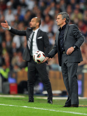 MADRID, SPAIN - APRIL 16:  Head coach Jose Mourinho (R) of Real Madrid throws the ball backdropped by head coach Josep Guardiola of Barcelona during the la Liga match between Real Madrid and Barcelona at Estadio Santiago Bernabeu on April 16, 2011 in Madr