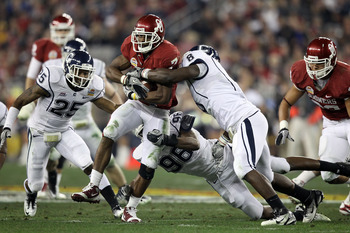 GLENDALE, AZ - JANUARY 01:  DeMarco Murray #7 of the Oklahoma Sooners  against the Connecticut Huskies attempts to take it away in the first half during the Tostitos Fiesta Bowl at the Universtity of Phoenix Stadium on January 1, 2011 in Glendale, Arizona