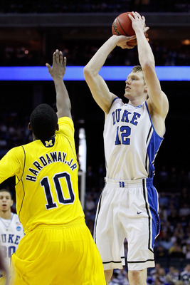 CHARLOTTE, NC - MARCH 20:  Kyle Singler #12 of the Duke Blue Devils shoots over Tim Hardaway Jr. #10 of the Michigan Wolverines during the third round of the 2011 NCAA men's basketball tournament at Time Warner Cable Arena on March 20, 2011 in Charlotte,