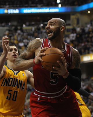 INDIANAPOLIS, IN - APRIL 23: Carlos Boozer #5 of the Chicago Bulls grabs a rebound in front of Tyler Hansbrough #50 of the Indiana Pacers in Game Four of the Eastern Conference Quarterfinals in the 2011 NBA Playoffs at Conseco Fieldhouse on April 23, 2011