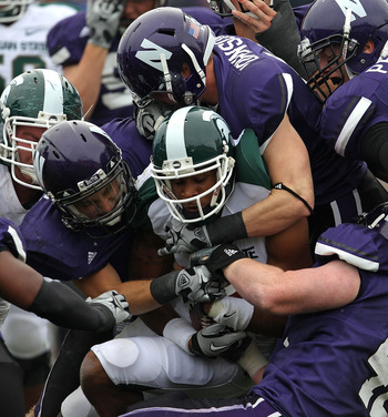 EVANSTON, IL - OCTOBER 23: B.J. Cunningham #3 of the Michigan State Spartans is stopped by (L-R) Hunter Bates #7, Ben Johnson #35 and Kevin Watt #42 of the Northwestern Wildcats at Ryan Field on October 23, 2010 in Evanston, Illinois. Michigan State defea