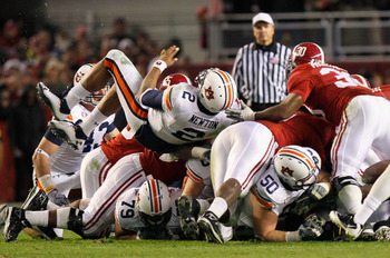 TUSCALOOSA, AL - NOVEMBER 26:  Quarterback Cam Newton #2 of the Auburn Tigers dives and rolls over the defense of the Alabama Crimson Tide for a first down at Bryant-Denny Stadium on November 26, 2010 in Tuscaloosa, Alabama.  (Photo by Kevin C. Cox/Getty